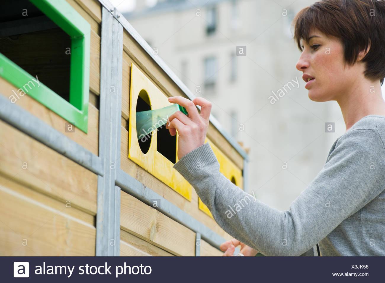 Mujer colocando la botella de plástico en la papelera de reciclaje Imagen De Stock