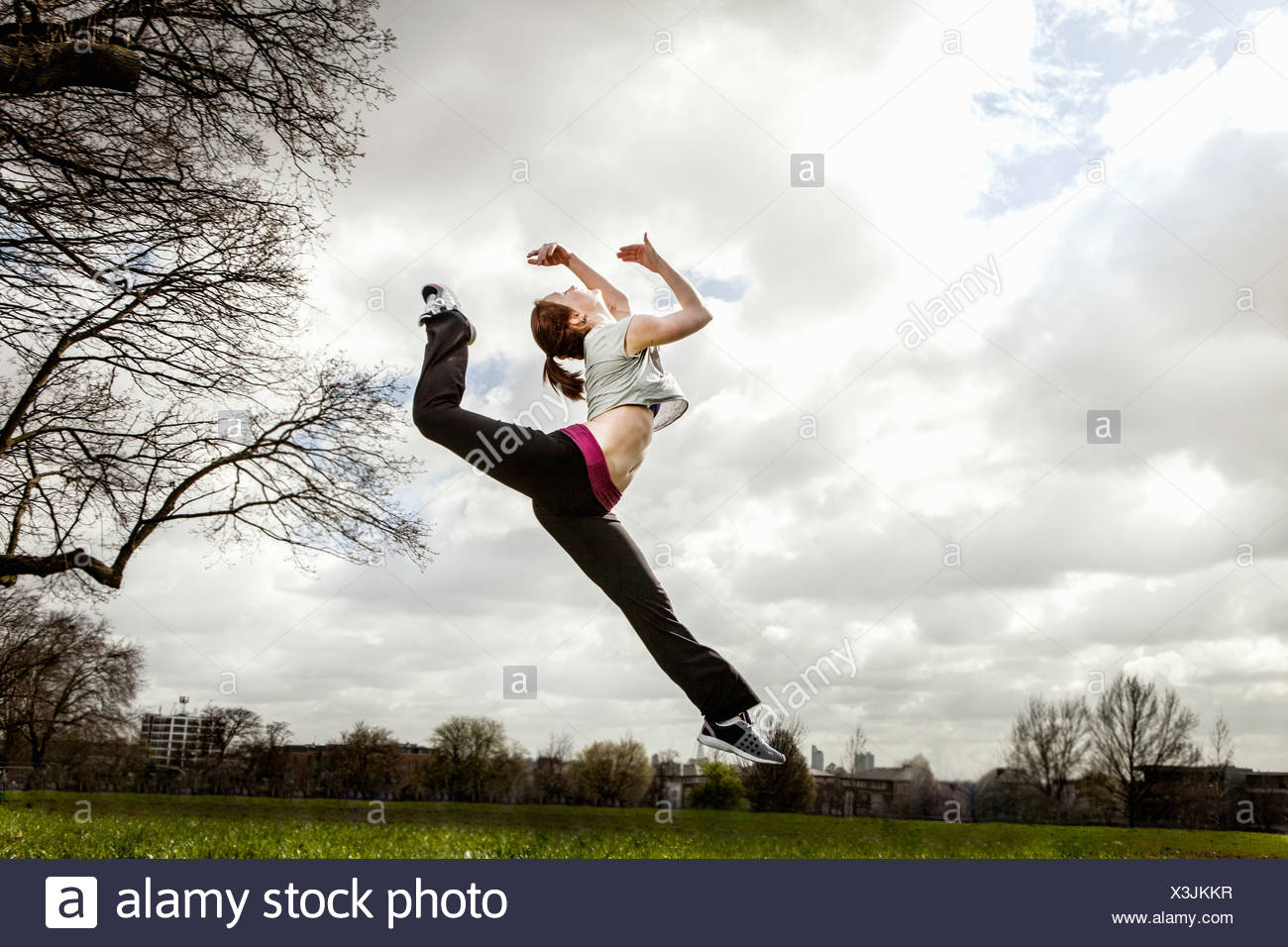Mujer saltando en medio del aire con la pierna doblada Imagen De Stock