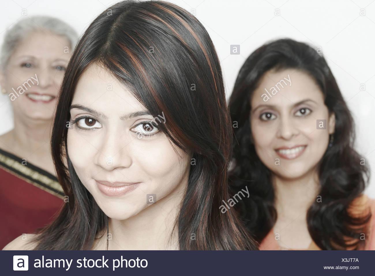 Retrato de una joven sonriente con dos mujeres de pie detrás de ella Imagen De Stock