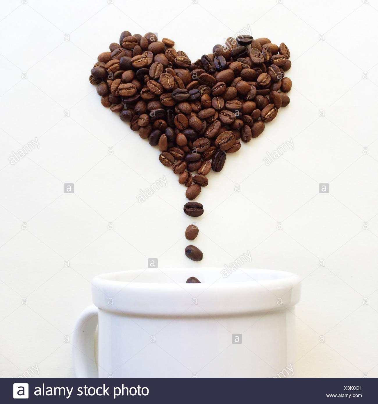 Los granos de café en forma de corazón cae en una taza de café Imagen De Stock