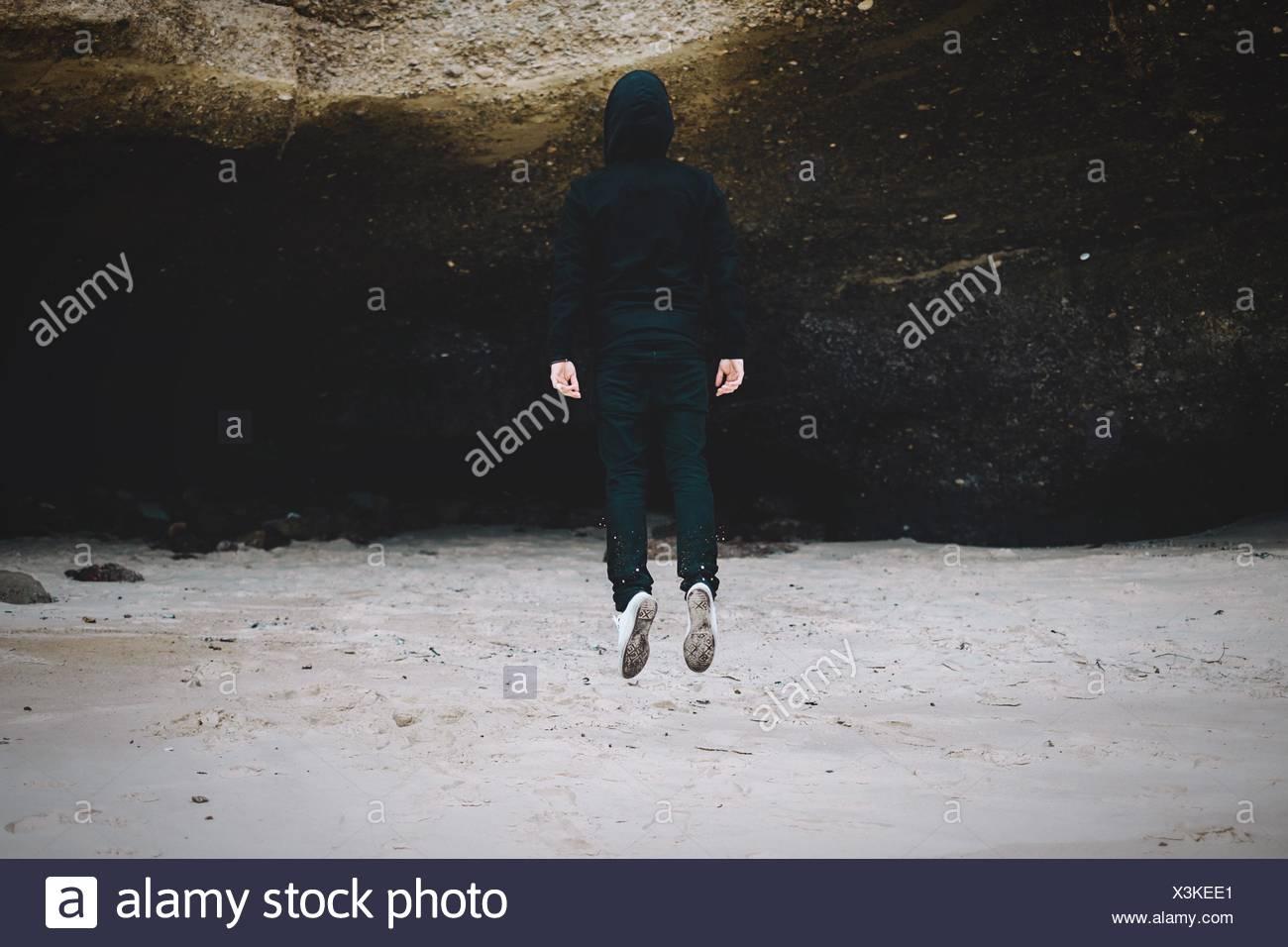 Vista trasera de una mujer saltando sobre el paisaje Imagen De Stock