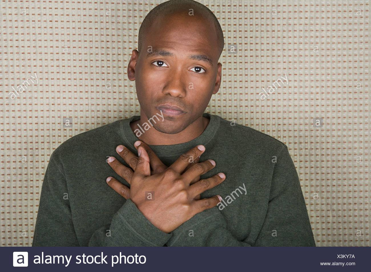Retrato de estudio de mediados de un hombre adulto con manos plegadas en el pecho Imagen De Stock