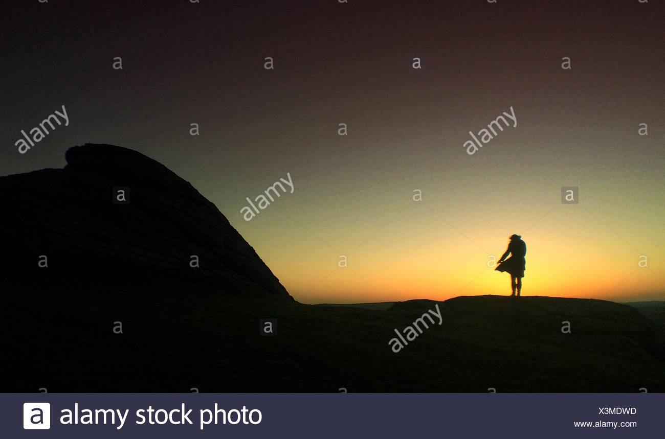 Silueta de Mujer de pie sobre las rocas Imagen De Stock