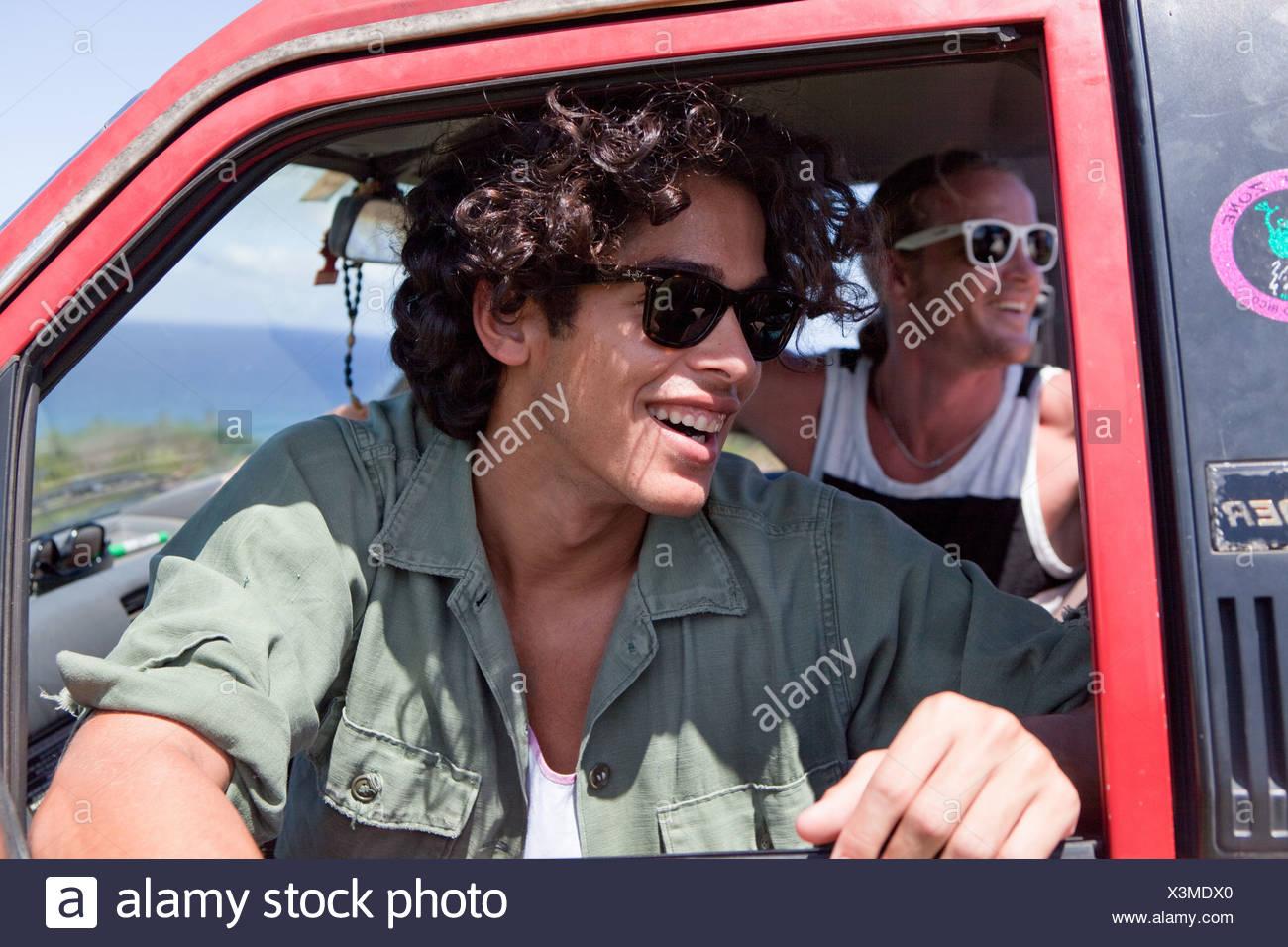 Dos hombres en busca de abrir ventana de coche en vacaciones Imagen De Stock