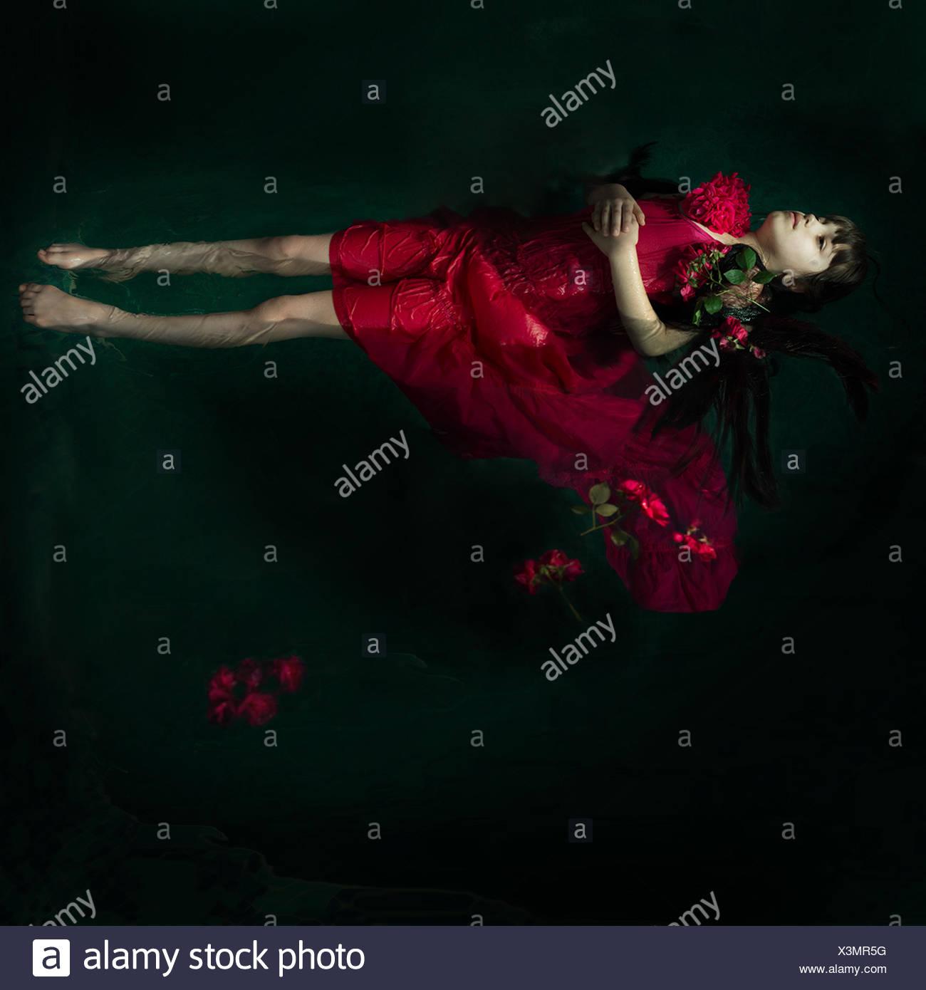 Chica en un vestido rojo flotando en el agua con rosas rojas Imagen De Stock
