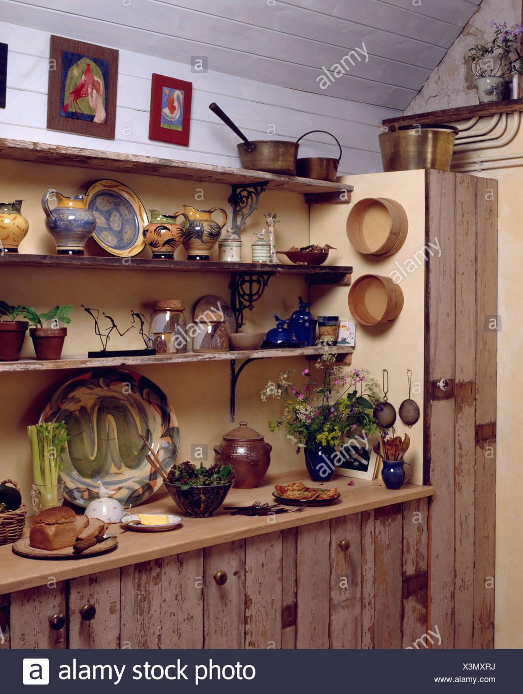 Platos de cerámica y la jarra en estanterías en casa cocina con unidades de  madera rústica 007d30990665