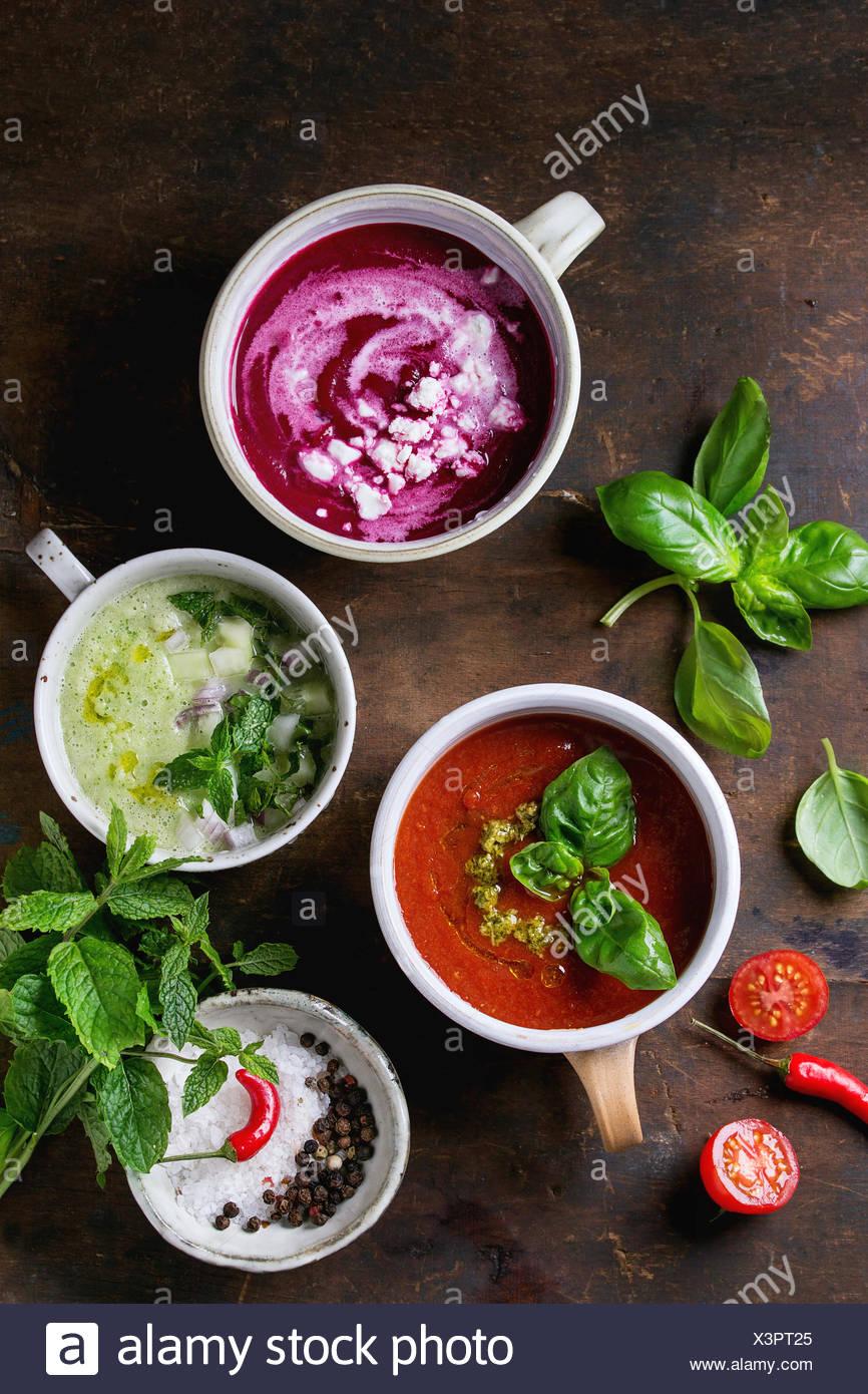 Variedad de sopas vegetarianas fría gazpacho de pepino con menta, remolachas con queso feta, tomate con pesto verde, servido con se Foto de stock