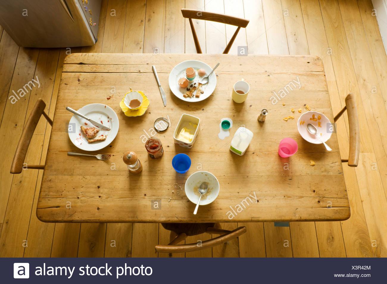 Vista aérea de la mesa de desayuno con comido alimentos y placas desordenadas Imagen De Stock