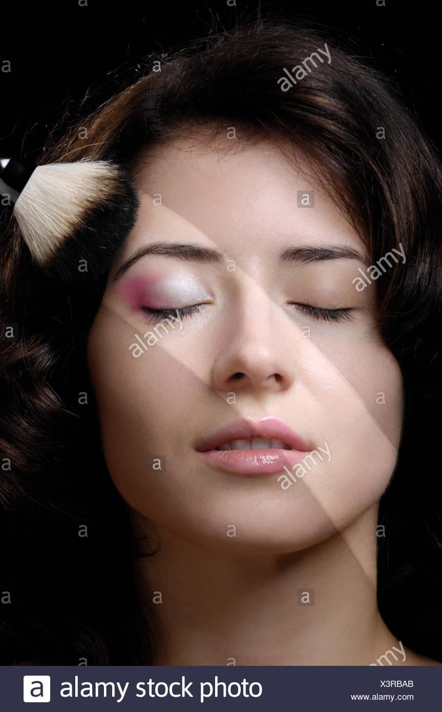 Pincel sobre el rostro de una joven mujer, tratamientos de belleza concepto Imagen De Stock