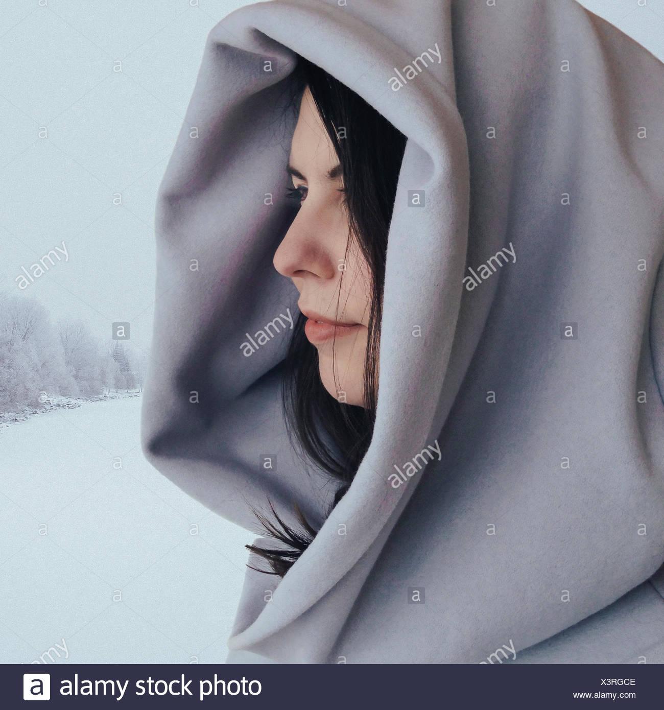 Retrato de una mujer que se encuentra en la nieve con un abrigo con capucha, Calgary, Alberta, Canadá Foto de stock
