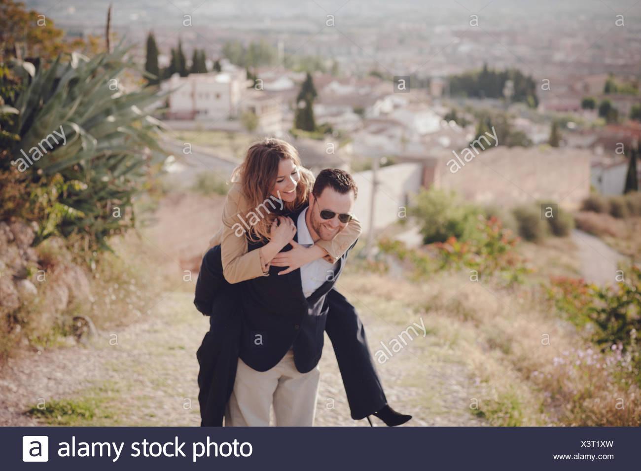 El hombre y la mujer haciendo Piggyback Ride Imagen De Stock