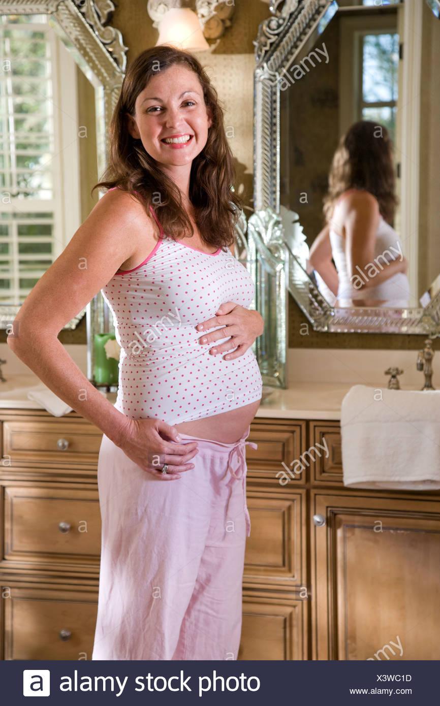 bb85acd1f500 Mujer embarazada por tocador de baño permanente en pijama Imagen De Stock