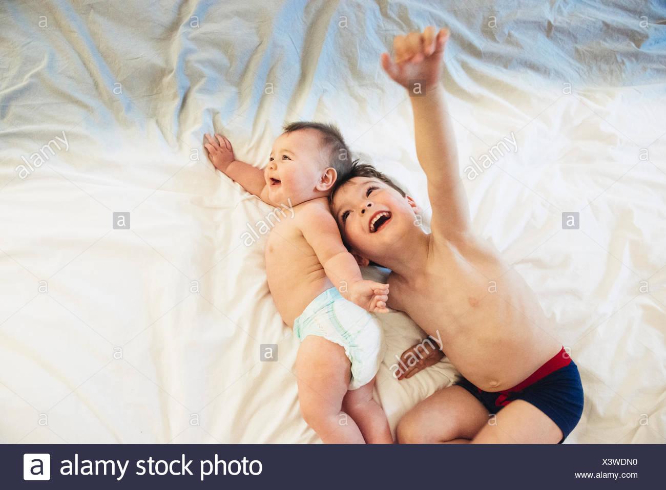 Dos niños, un hermano y una hermana de bebé acostado jugando juntos. Imagen De Stock