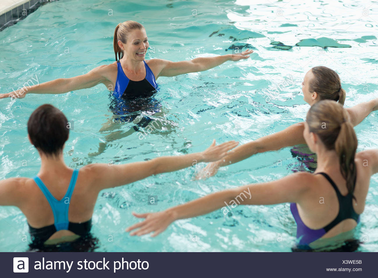 Las mujeres que toman clase de aeróbicos de agua Imagen De Stock