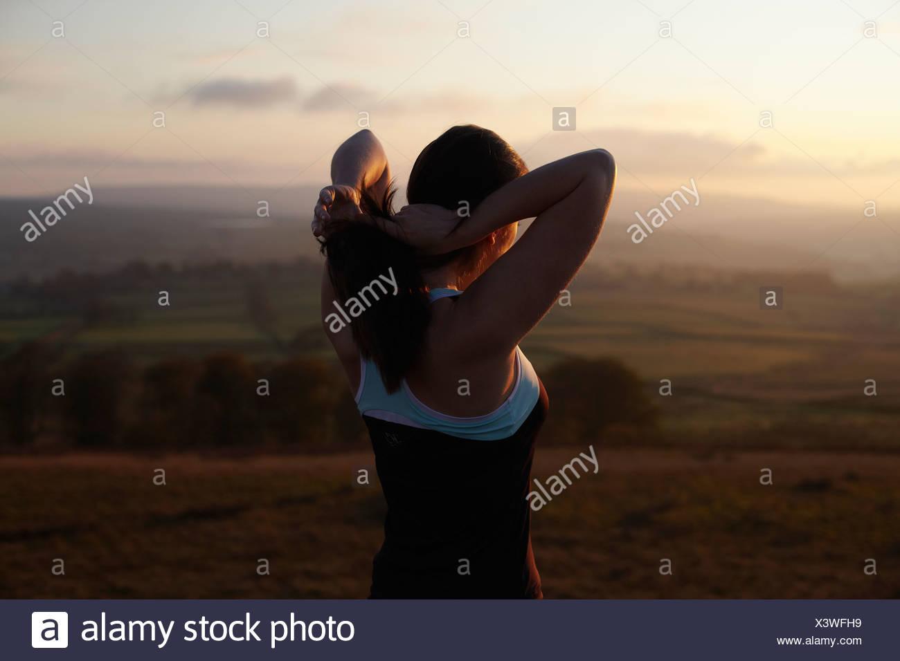 Runner atando su cabello en el paisaje rural Imagen De Stock