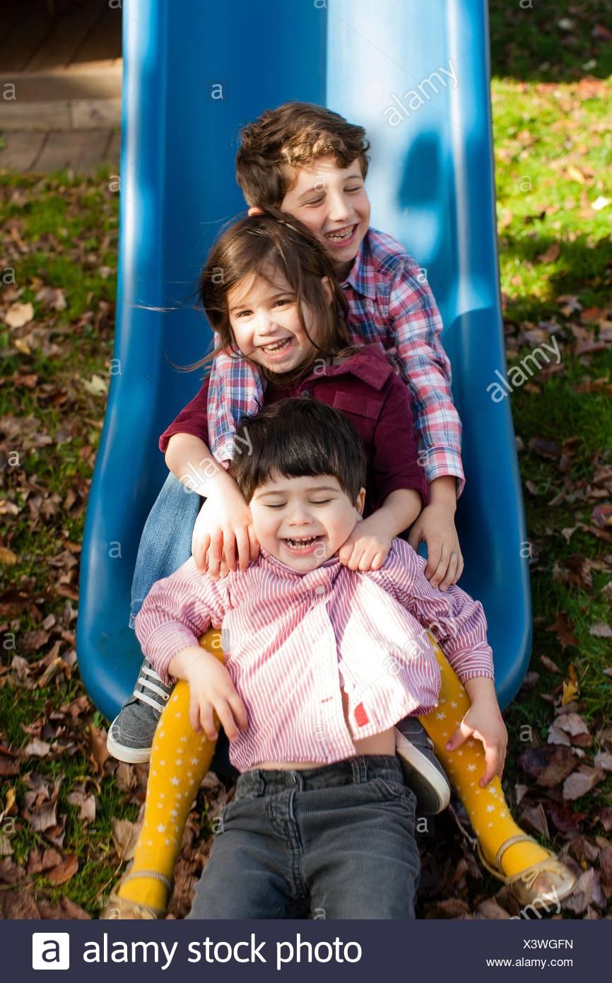 Los hermanos en una fila entre otras piernas en playground deslice sonriendo Imagen De Stock