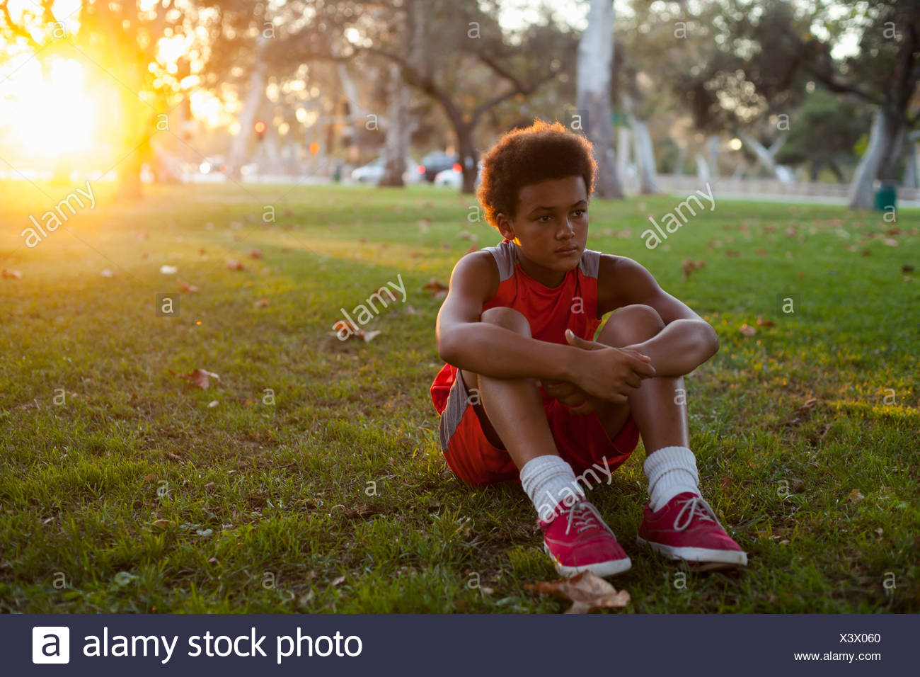 Triste buscando muchacho sentado en el parque Imagen De Stock