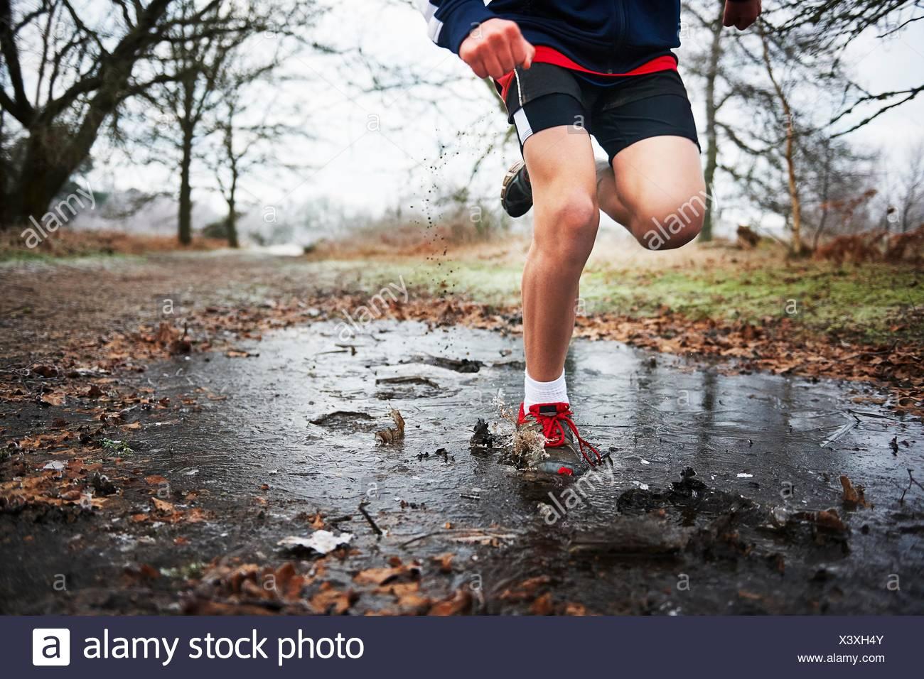 Vista frontal de la adolescente corriendo a través de la charca Imagen De Stock