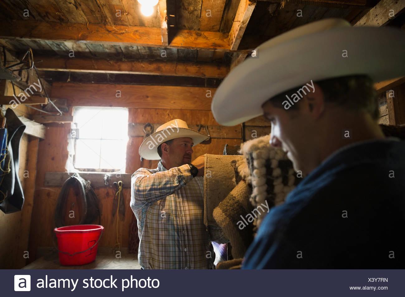 Los rancheros ajuste mantas en el granero Imagen De Stock