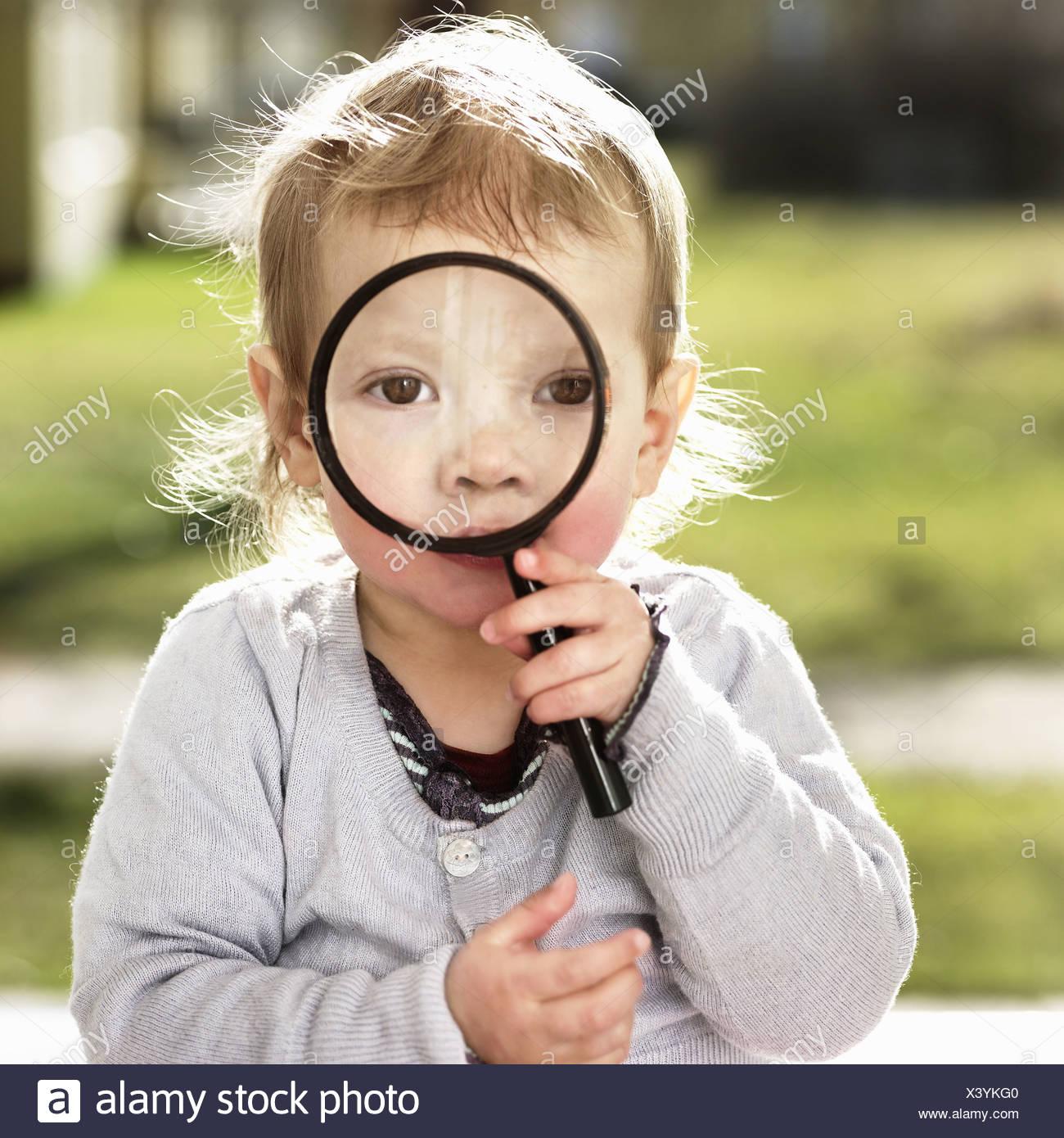 Niñito Chica sujetando la lupa Imagen De Stock
