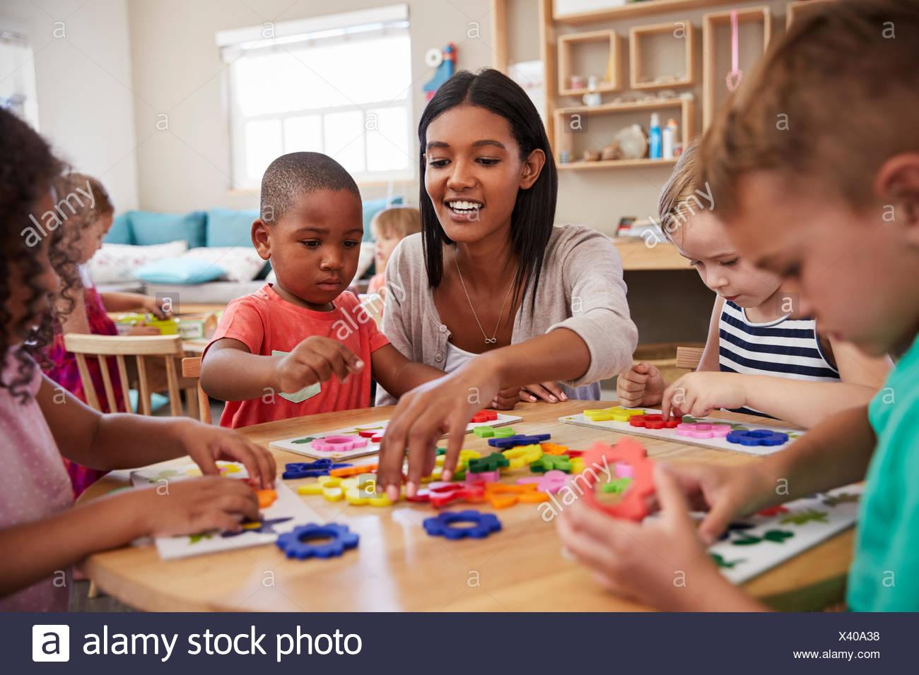 El profesor y los alumnos mediante formas florales en Montessori School Imagen De Stock