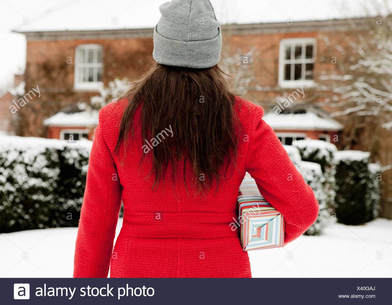 Mujer llevar regalos envueltos en la nieve Foto de stock