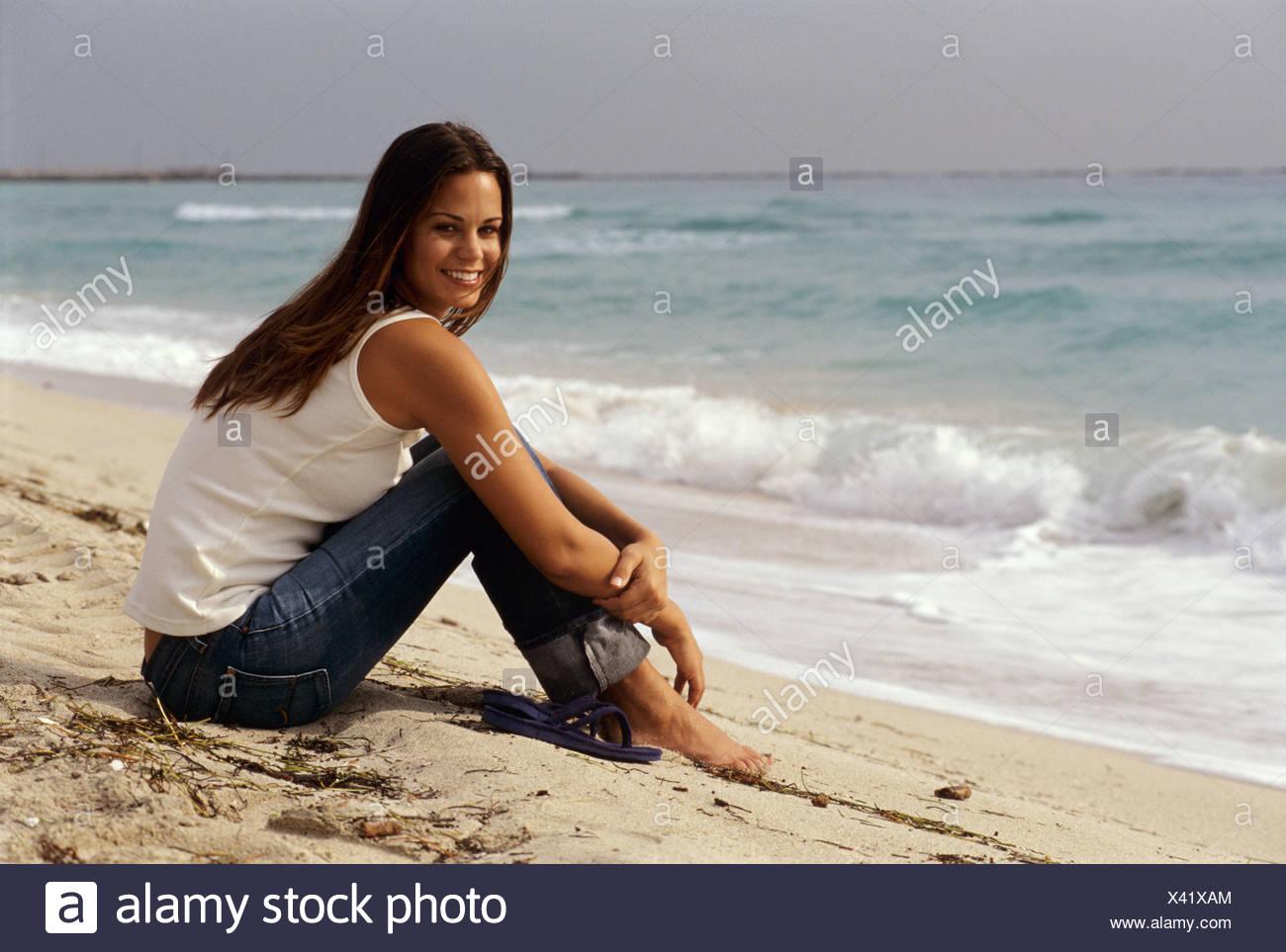 Perfil semi largo cabello morena de mujeres vestidas de blanco chaleco top  y pantalones vaqueros azul 98b9fdb649b0