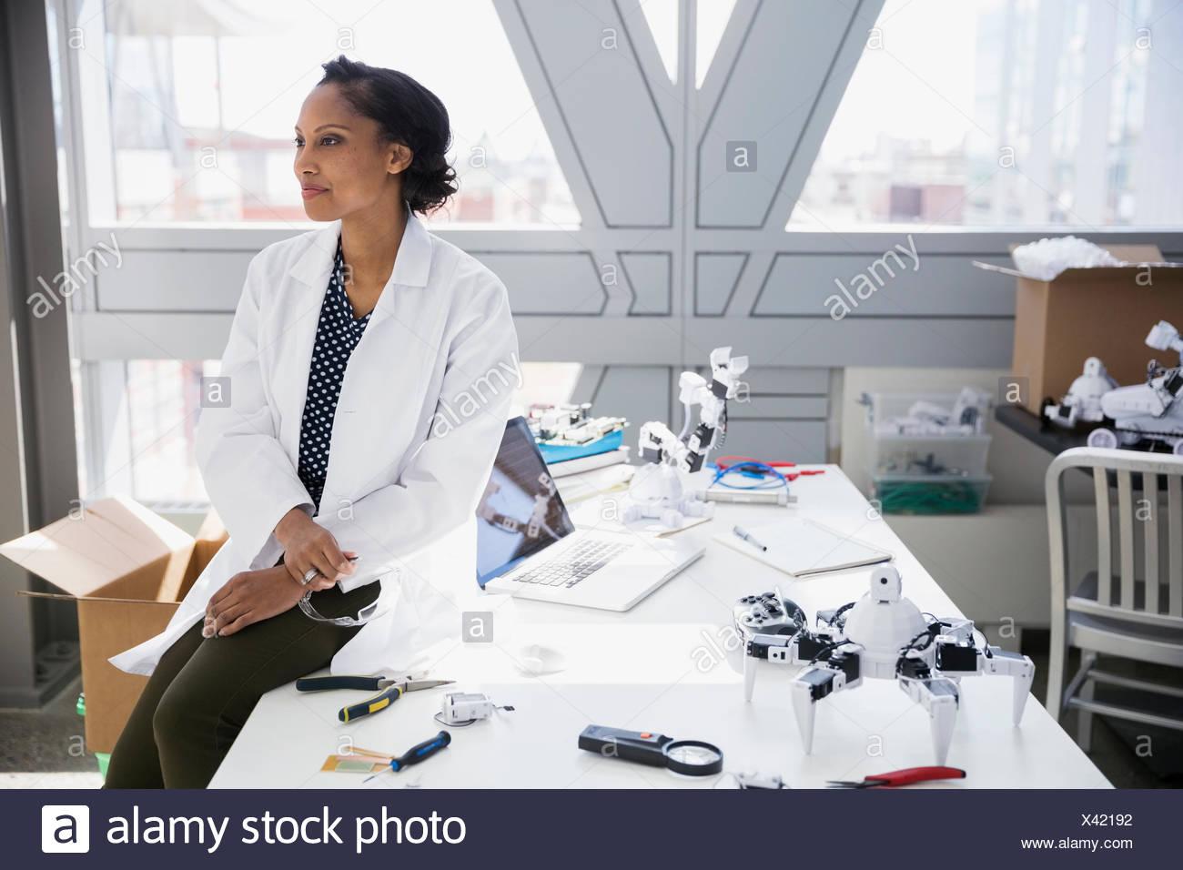 Ingeniero pensativo y escritorio con robots Imagen De Stock
