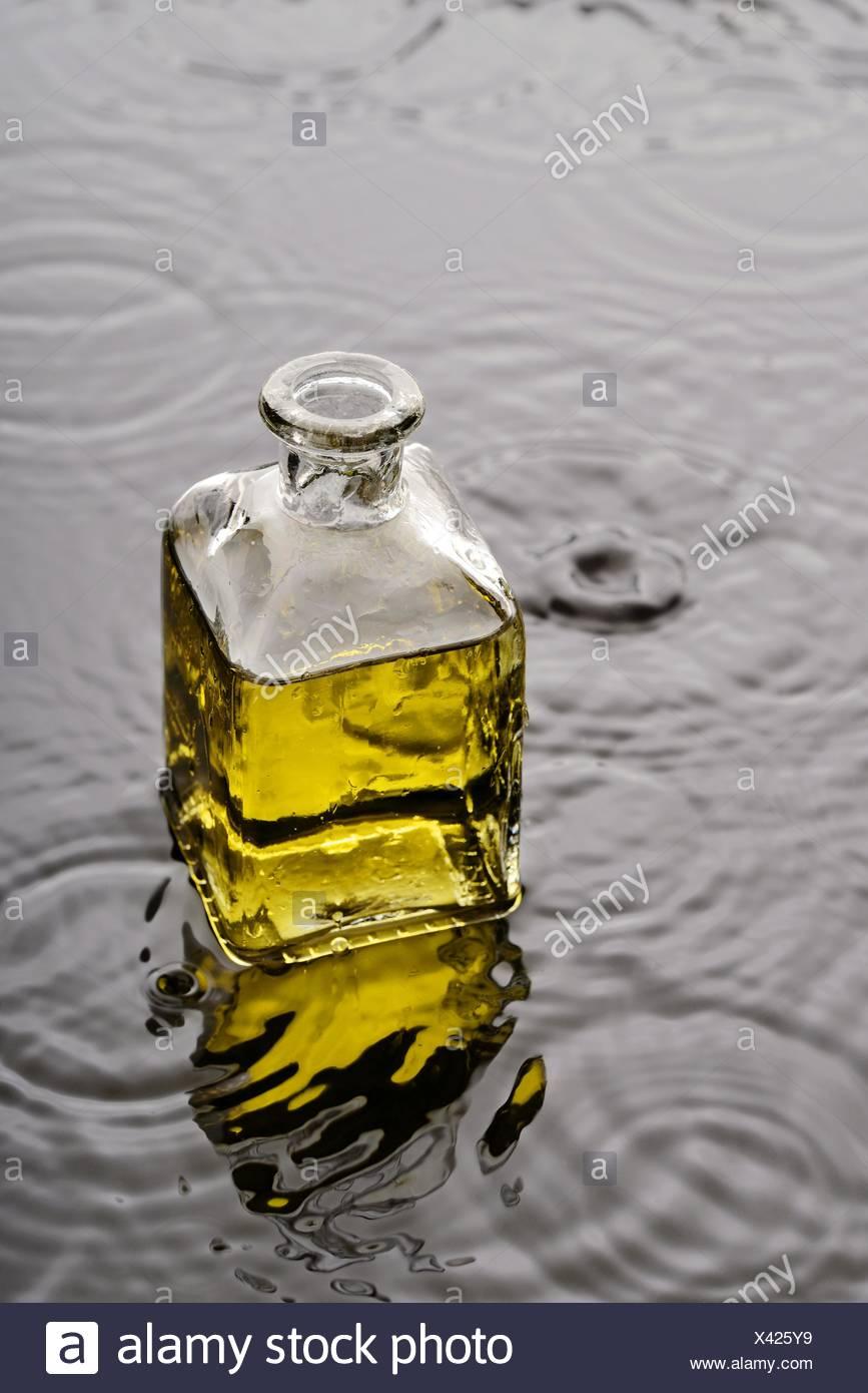 Líquido amarillo, aceite o perfume, en un frasco de vidrio sobre el agua con gotas de agua y ondas. Imagen De Stock
