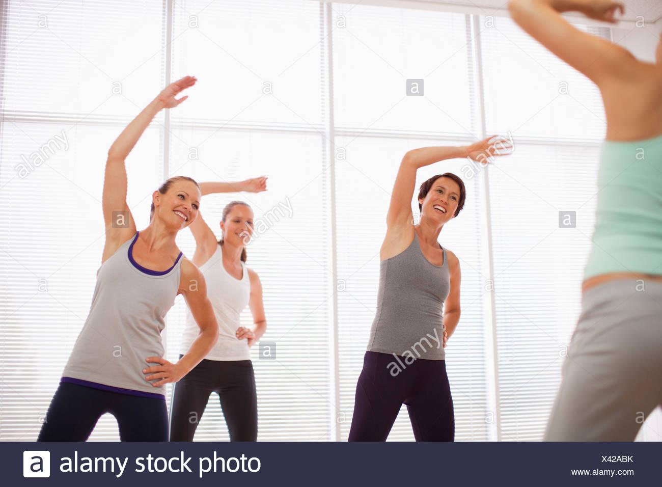 Las mujeres con los brazos levantados en clase de ejercicios Imagen De Stock