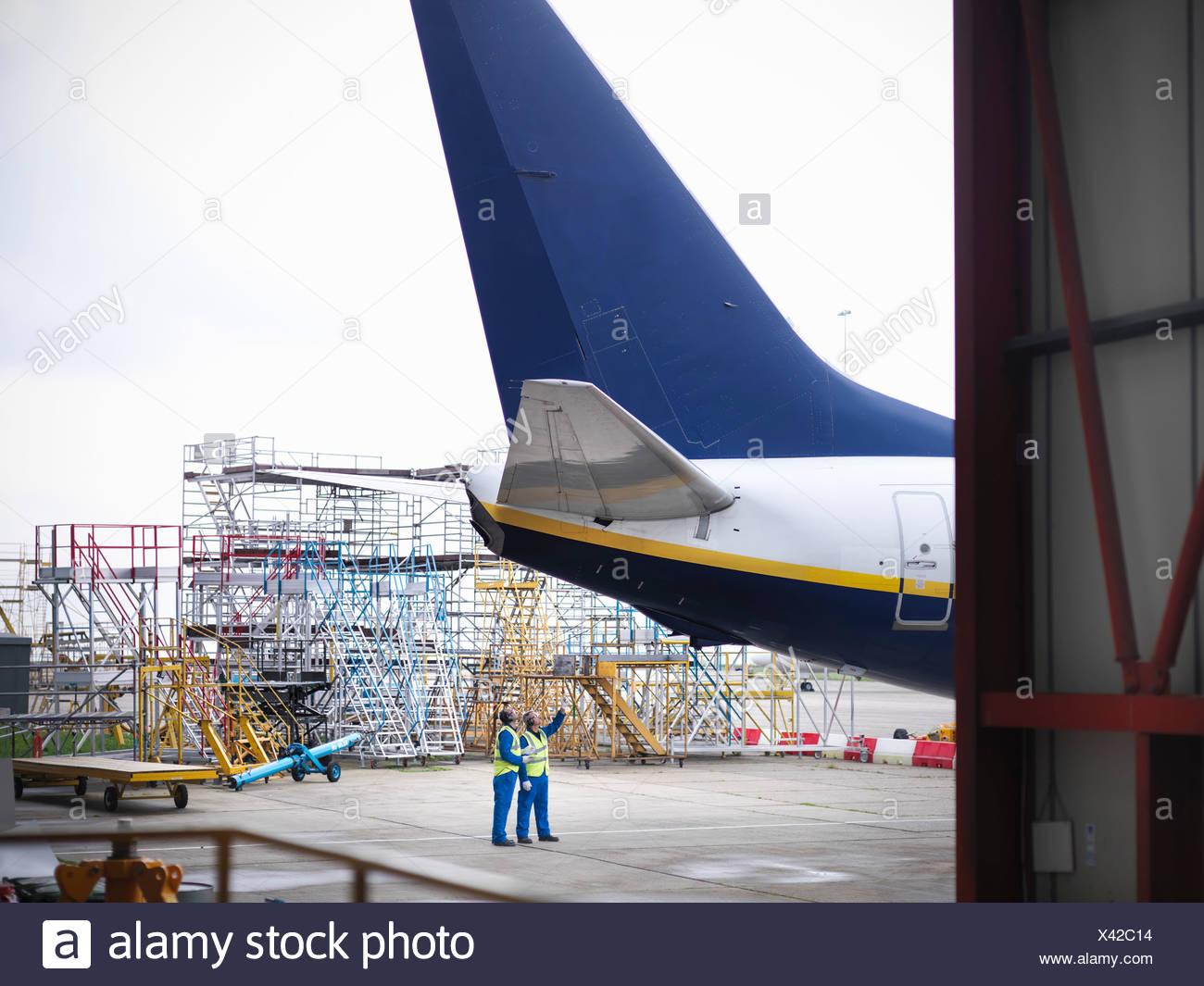 Los trabajadores examinando la parte inferior del avión Imagen De Stock