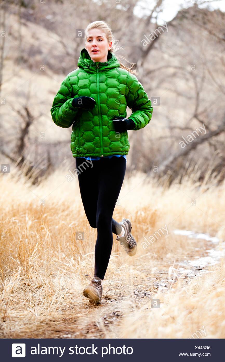 Una joven mujer corre un sendero hacia abajo a través de la hierba muerta, justo al norte del depósito de Dixon, en un día frío en un verde Down Jacket. Imagen De Stock