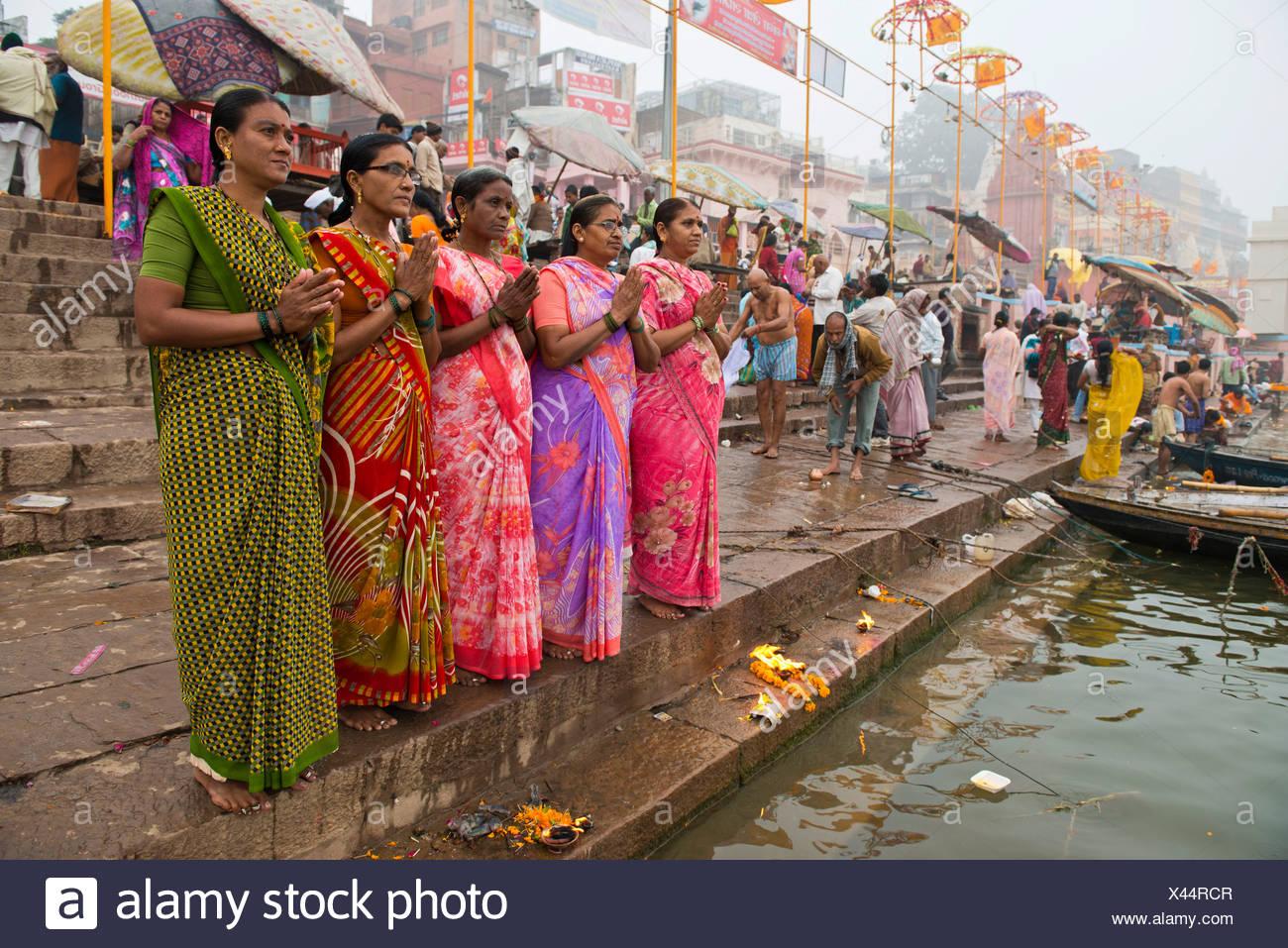 Cinco mujeres en saris coloridos en la oración, a orillas del río Ganges, Varanasi, Uttar Pradesh, India Imagen De Stock