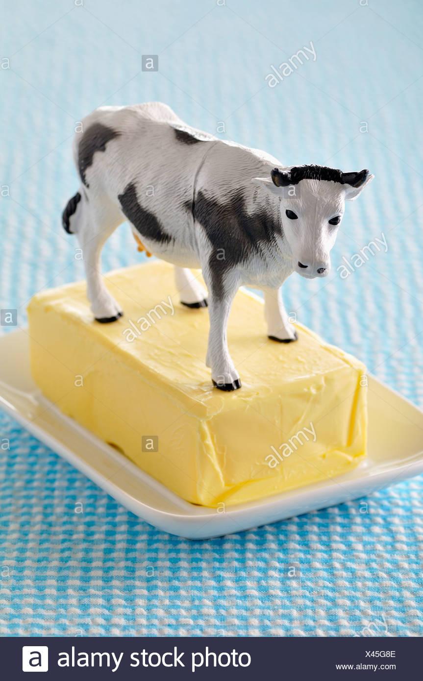 Plastico vaca en una losa de mantequilla Imagen De Stock