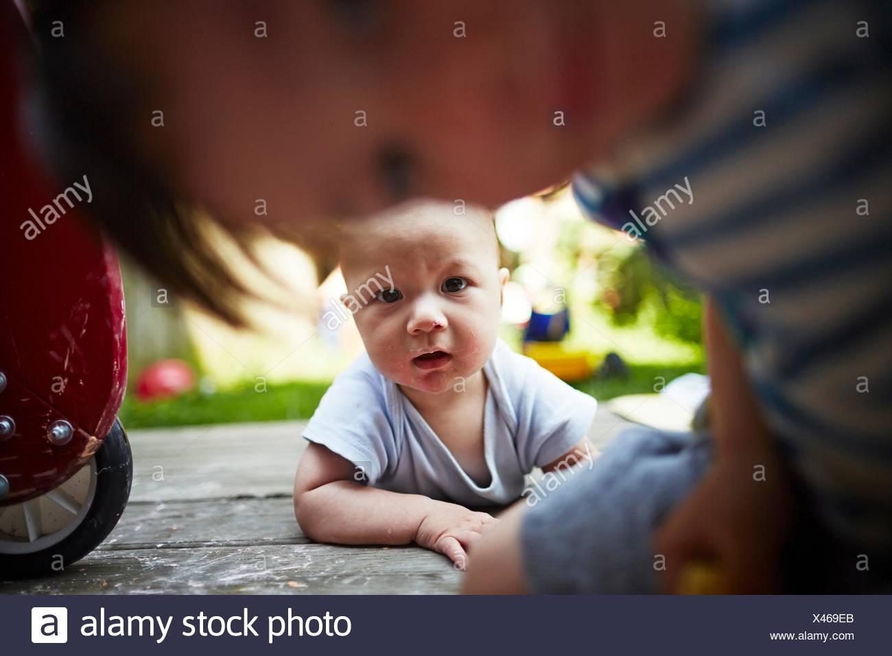 Retrato de Baby Boy acostada mirando a la cámara con su hermano mayor en primer plano Imagen De Stock