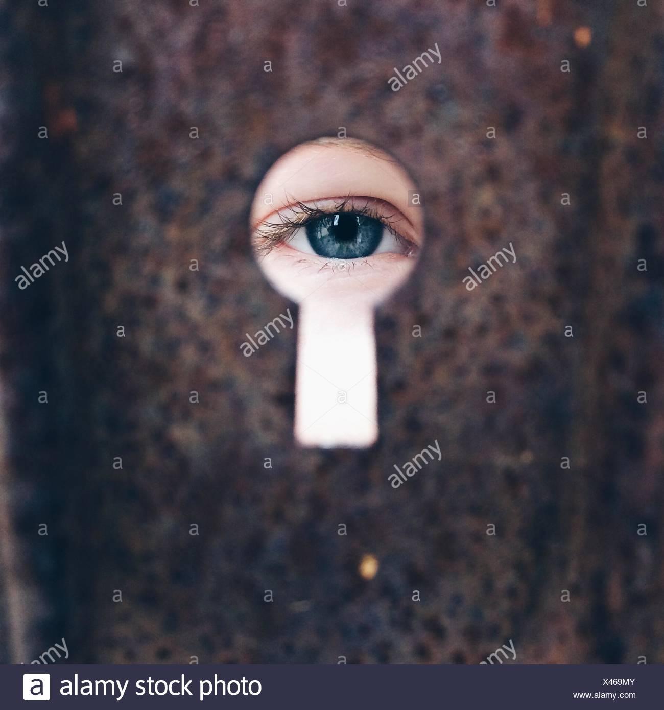 Chica (8-9) mirando a través de keyhole Imagen De Stock