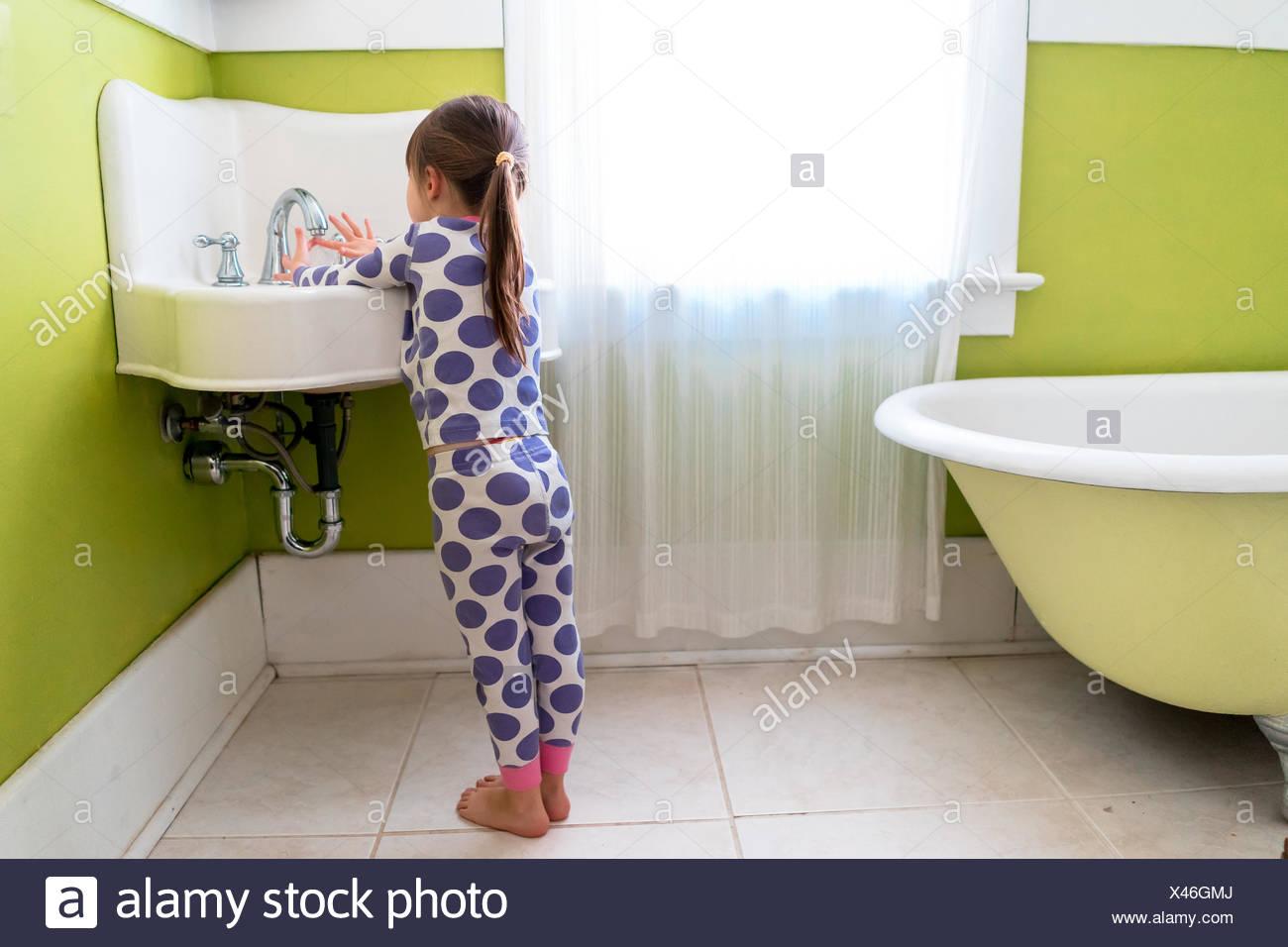 Chica de pie en el baño, lavando sus manos Foto de stock