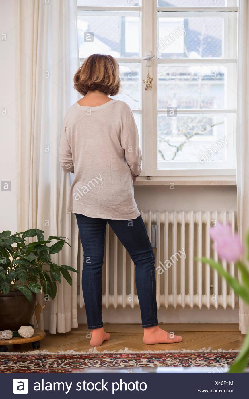 Vista trasera de altos mujer mirando por una ventana, Munich, Baviera, Alemania Foto de stock