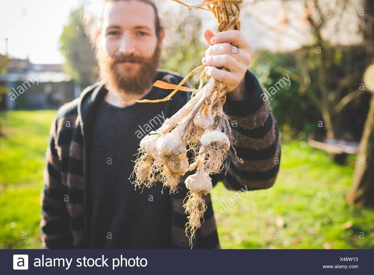 A mediados barbudo hombre adulto en el jardín la celebración recién elegido bulbos de ajo mirando a la cámara sonriendo Imagen De Stock