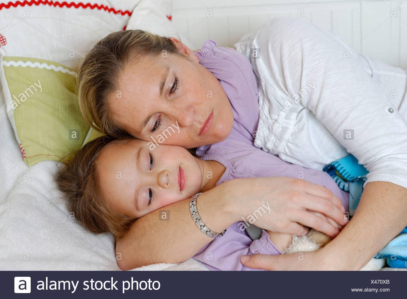 Madre e hija caricias en la cama, abrazando Imagen De Stock