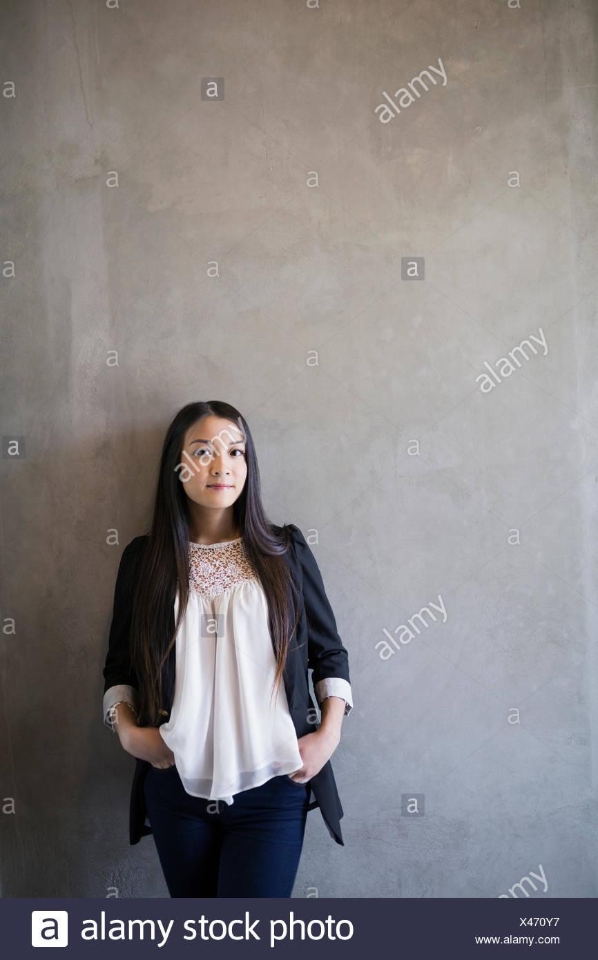 Retrato mujer confiada con las manos en los bolsillos de fondo gris Imagen De Stock