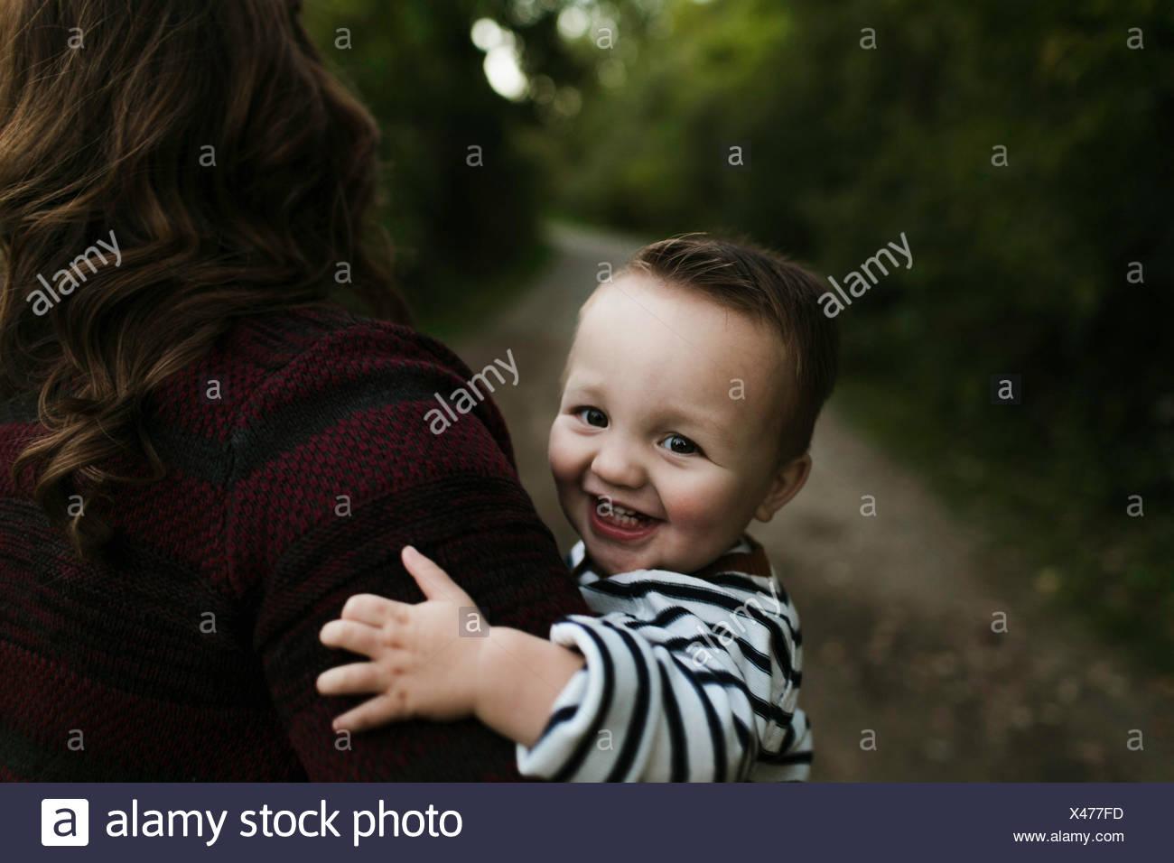 Baby Boy en brazos de la madre sonríe mirando a la cámara Imagen De Stock