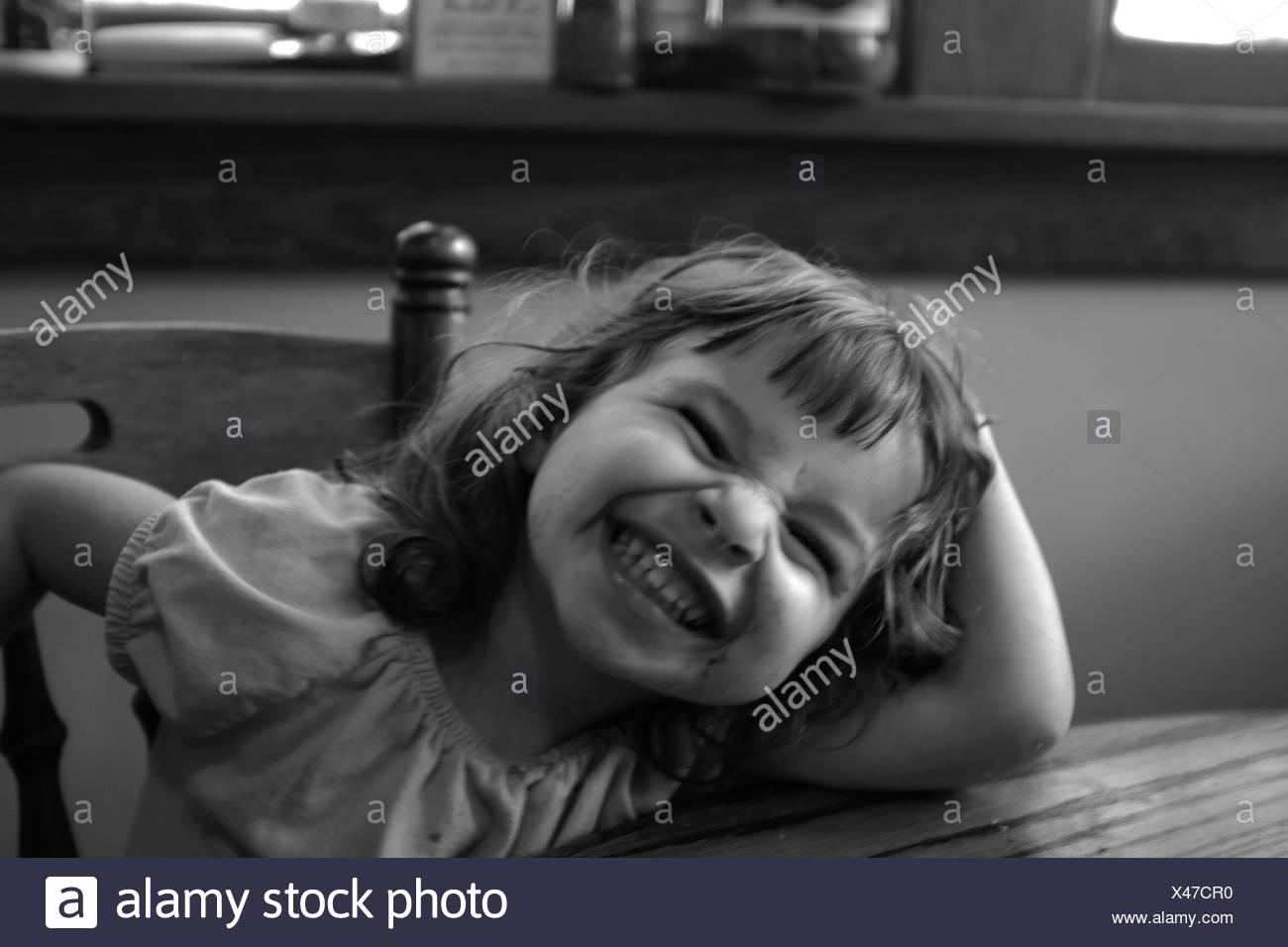 Niña feliz haciendo cara mientras estaba sentado en una silla Imagen De Stock