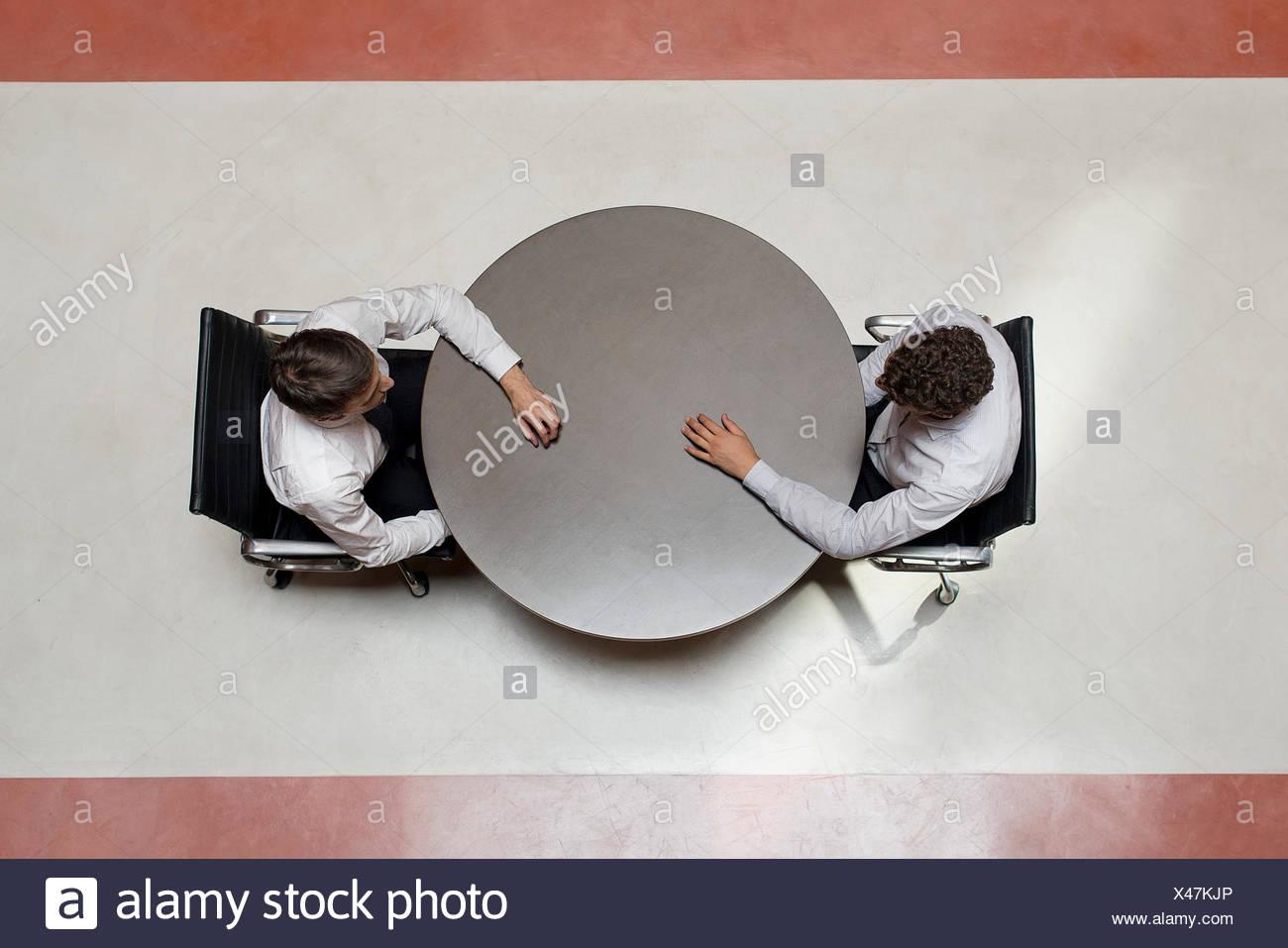 Los empresarios stting uno frente a otro Imagen De Stock