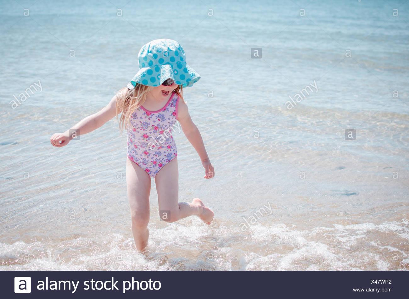 Chica salpicaduras en el mar Imagen De Stock