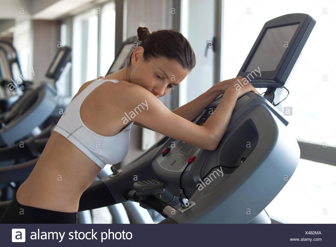 Mujer con máquina de ejercicio en el club de la salud Imagen De Stock