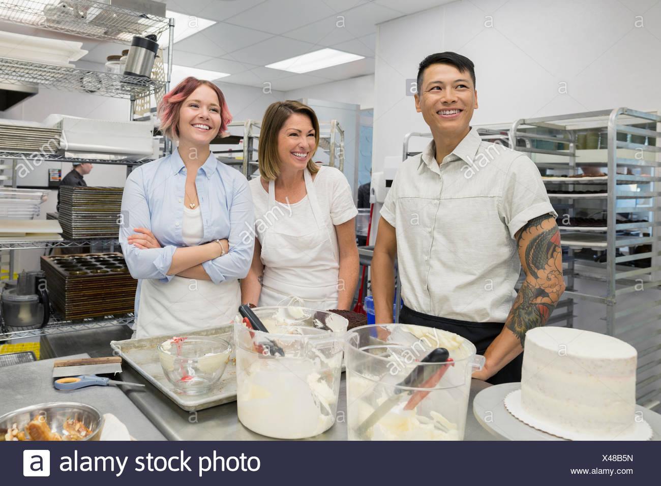 Laughing pasteleros en cocina comercial Imagen De Stock