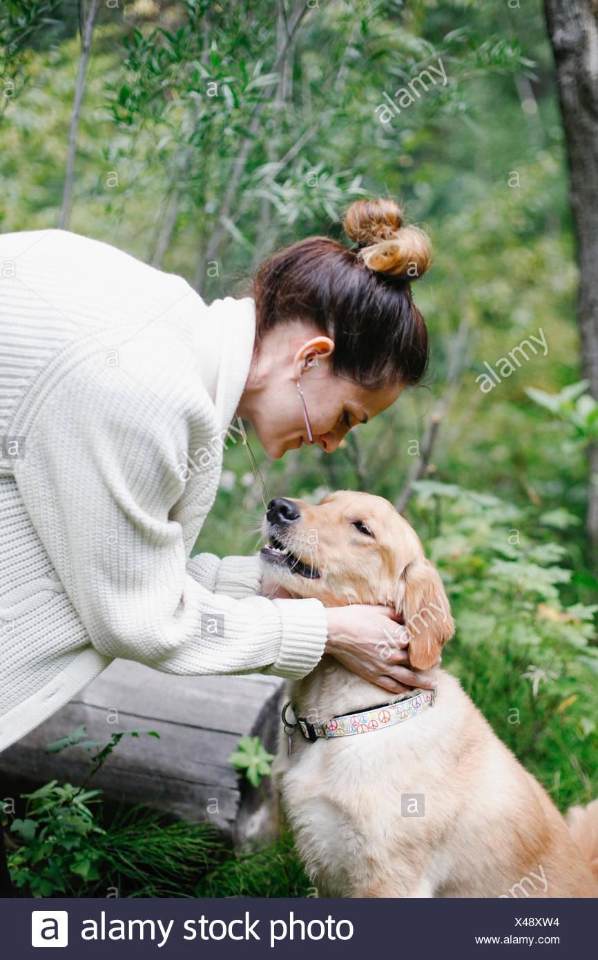 Una mujer acariciar a su perro. Imagen De Stock