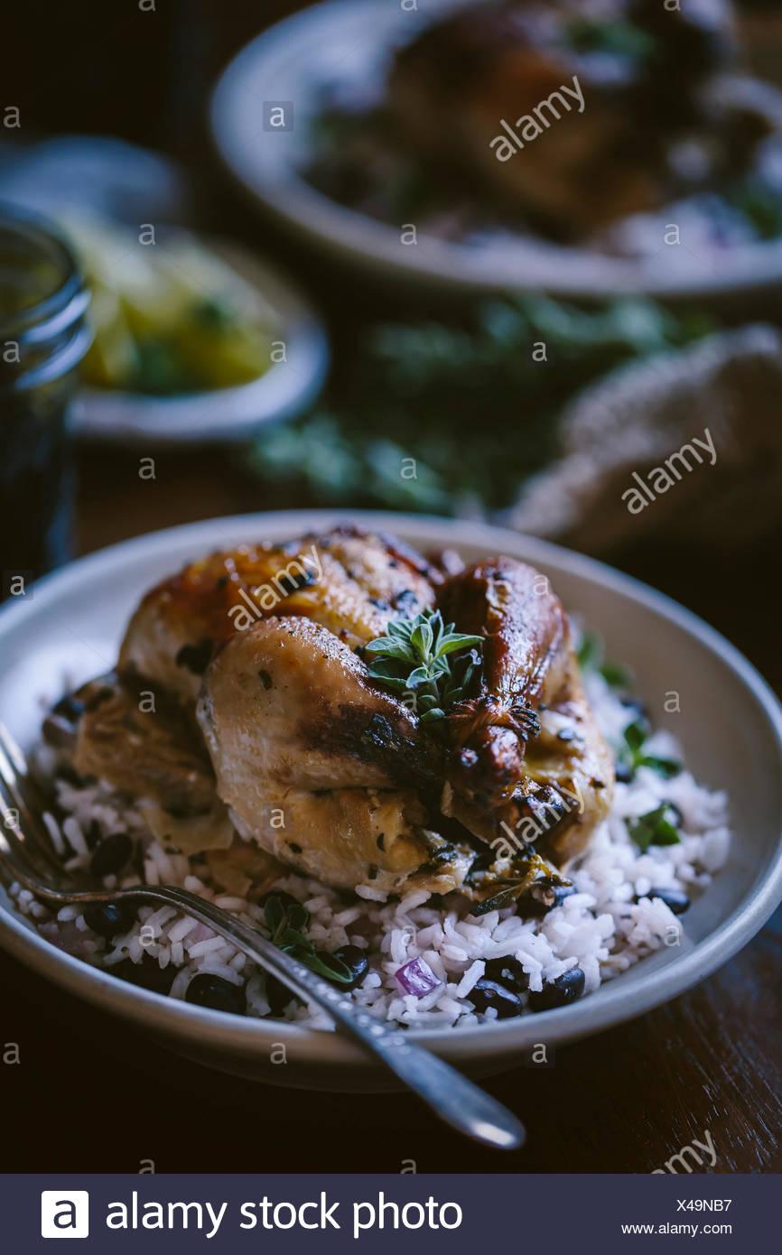 Un juego asado gallina sirve encima del arroz frijoles negros es fotografiado desde la vista frontal Imagen De Stock