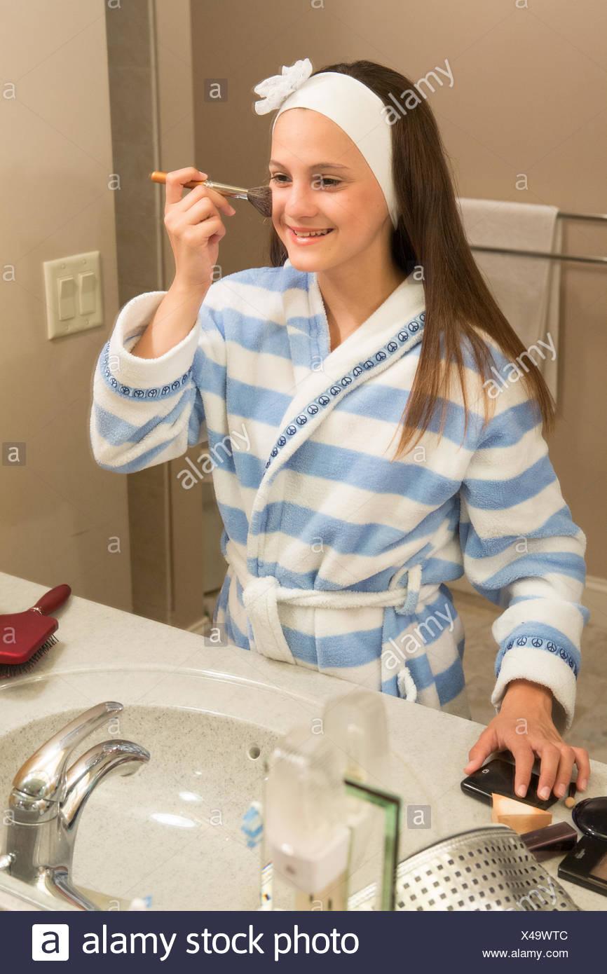 Joven (12-13) mirando en el espejo durante la aplicación de maquillaje Imagen De Stock